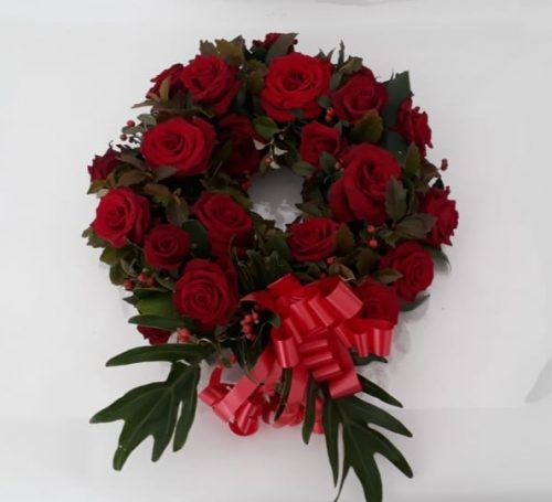 Round wreath with roses and greenery. Please specify choice of rose colour. Available in Port Elizabeth and surrounding areas.